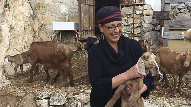 Efrat Giat holding a baby goat in the backyard of her home in Ein Kerem (Photo: Madison Dudley/The Media Line
