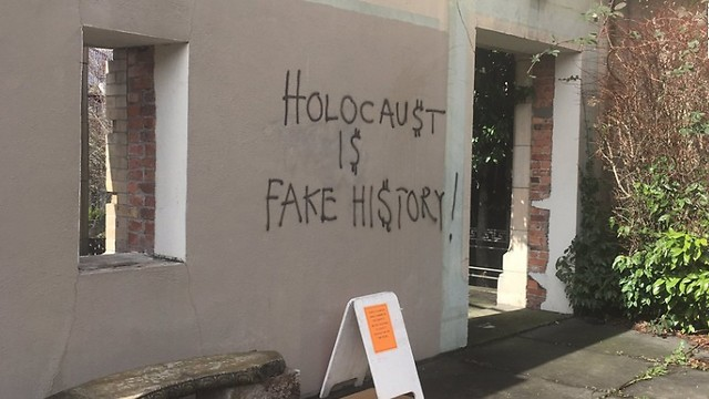 An exterior wall of the synagogue, spray-painted with a Holocaust denying message
