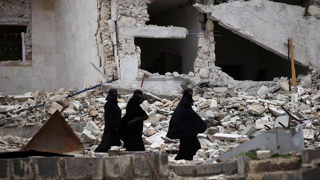 מדינה הרוסה. נשים סוריות הולכות בין ההריסות בעיר אל-באב (צילום: רויטרס)