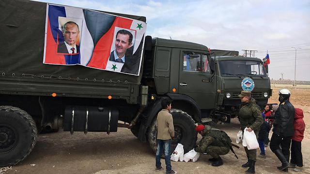 נשיא סוריה האמיתי. תמונות של פוטין ואסד על משאית של צבא רוסיה שמחלקת אספקה לפליטים בחלב (צילום: MCT)