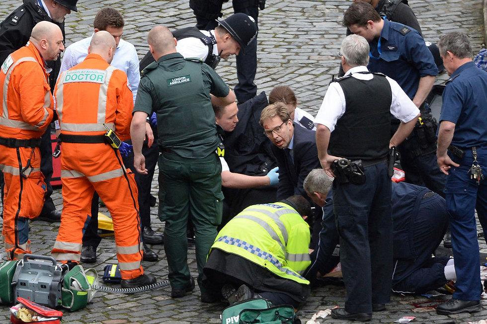 חבר הפרלמנט טוביאס אלווד מנסה להציל את חייו של השוטר (צילום: AP)