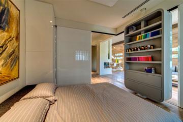 טיפ 2: קירות חדר השינה נעים על מסילות וחלק אף מסתובב על ציר - בצד אחד ספרייה ובשני מסך טלוויזיה. דירה בתכנון הילה הולנדר (צילום: איתי סיקולסקי)