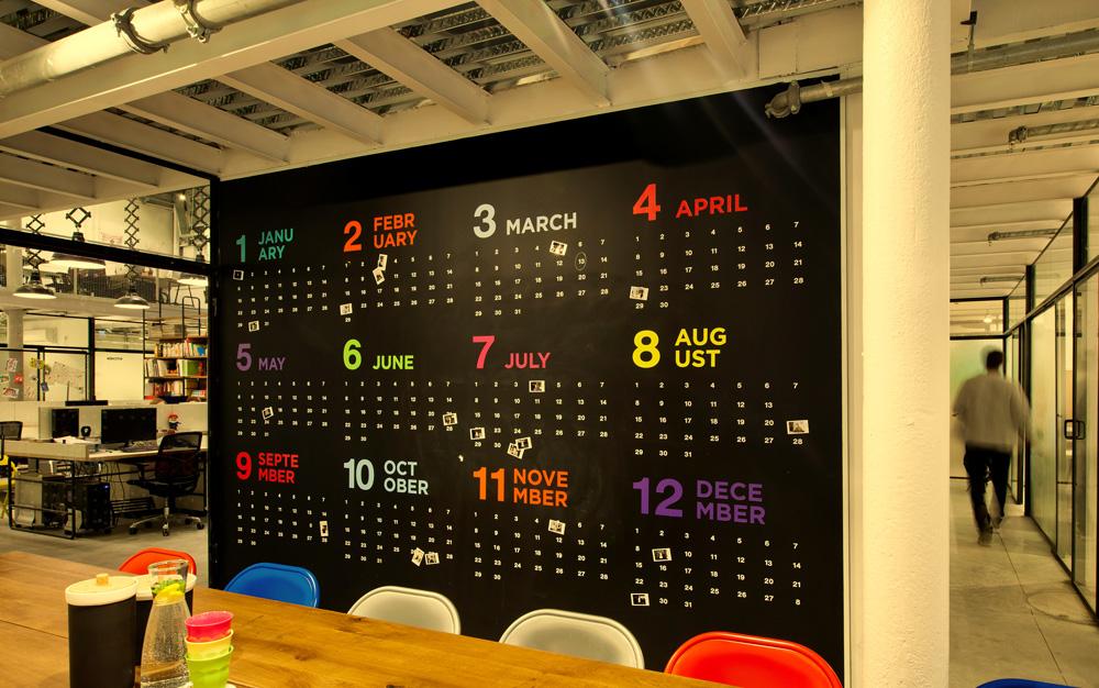 בפינת המטבח שולחן עץ ארוך מוקף בכסאות מתקפלים צבעוניים, לצד קיר שנצבע בצבע לוח ועליו צויר לוח שנה גדול (עיצוב: אדווה הופשטיין) (צילום: בועז לביא ויונתן בלום)