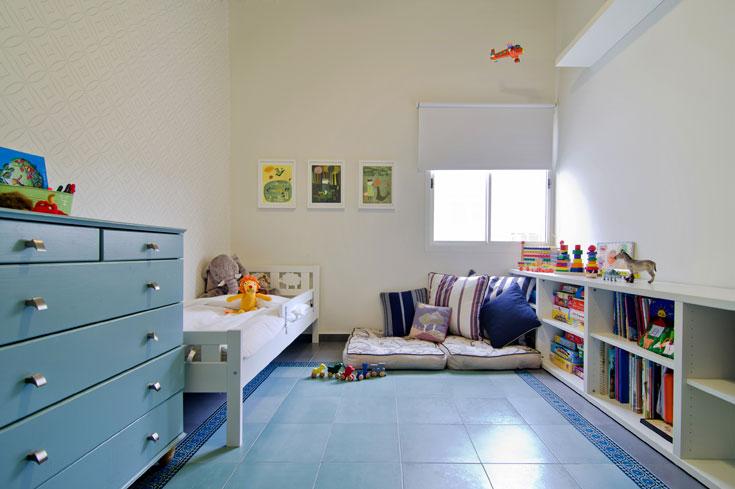 שימוש בצבע גם בחדר הילדים, עם טפט גיאומטרי, מרצפות מצוירות באפור וטורקיז ואיורים שהוזמנו באינטרנט ומוסגרו (צילום: אילן נחום)