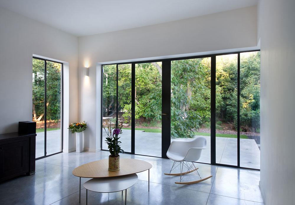 רצפת הבטון של הסלון ''יוצאת'' החוצה דרך החלון, ומרחפת מעל לאדמה בחצר. הבמה שנוצרה יכולה לשמש למופעי מוזיקה אינטימיים (בני הבית שניהם מוזיקאים) (צילום: עמית גושר)