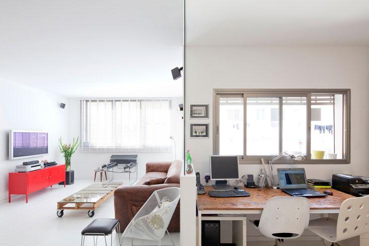 בין הסלון לפינת העבודה המרווחת מפרידים חצי קיר ומחיצת זכוכית (צילום: אביעד בר נס)