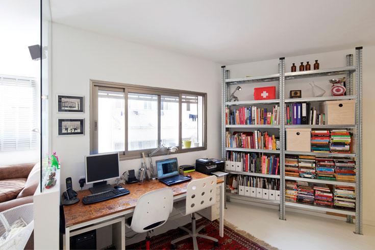 גם שולחן העבודה נבנה בידי בני הזוג, מפלטת שבבי עץ ורגלי ברזל. מדפי ספרים תעשייתיים מעניקים לקיר צבע ועניין (צילום: אביעד בר נס)