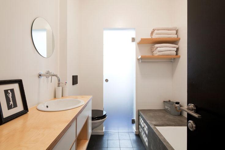 האמבטיה נוצקה מבטון מוחלק, עם ''כוורת'' לגלילי נייר טואלט ובמה שנמשכת עד הקיר (צילום: אביעד בר נס)