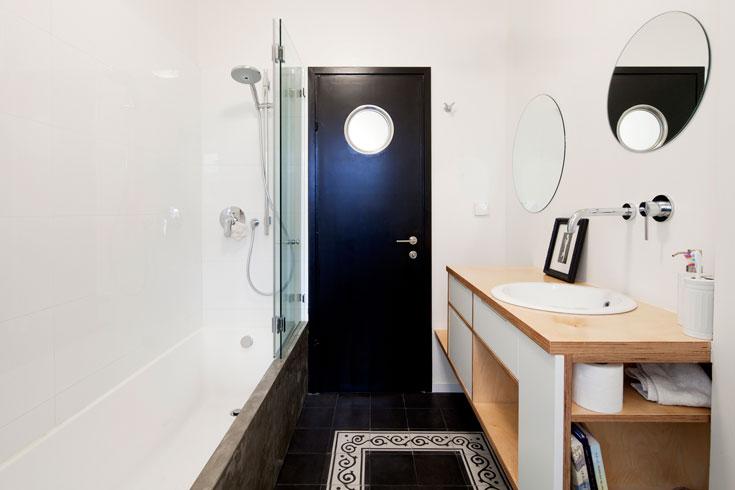 חדר הרחצה בעל אלמנטים שחורים חוזרים: מהדלת והרצפה ועד לחצן הניאגרה ומכסה האסלה (צילום: אביעד בר נס)