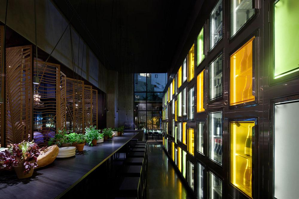 לאורך הקיר נבנה מקרר בירה ויין. דלתות הנירוסטה שובצו בזכוכית צבעונית, שמרמזת על צבעי התבלין שנמצאים במנות עצמן (צילום: עמית גרון)