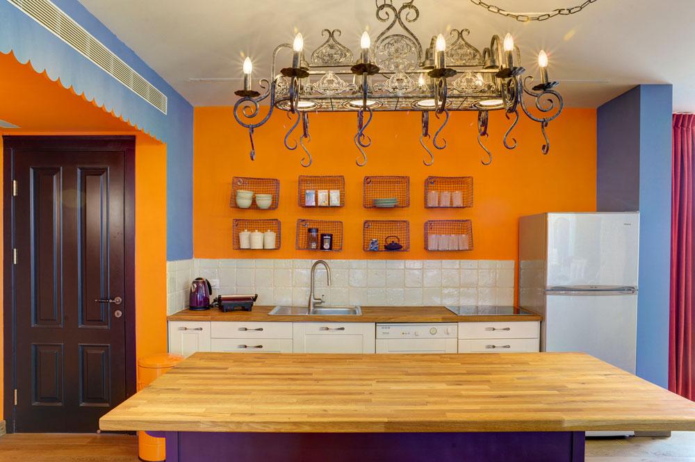 המטבח נצבע בכתום ו''מוסגר'' בכחול (משמאל דלת הכניסה לדירה). למטה ארונות לבנים פשוטים מ''איקאה'', שעליהם הוברגו ידיות שהוכנו ממזלגות. ה''אי'' נצבע סגול (צילום: Hadrien Daudet)