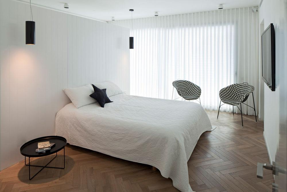 חדר ההורים, בשחור-לבן. מאחורי המיטה רהיט שהוזמן במיוחד. הכיסאות הם בעיצוב פאולה נבונה (צילום: עמית גרון)