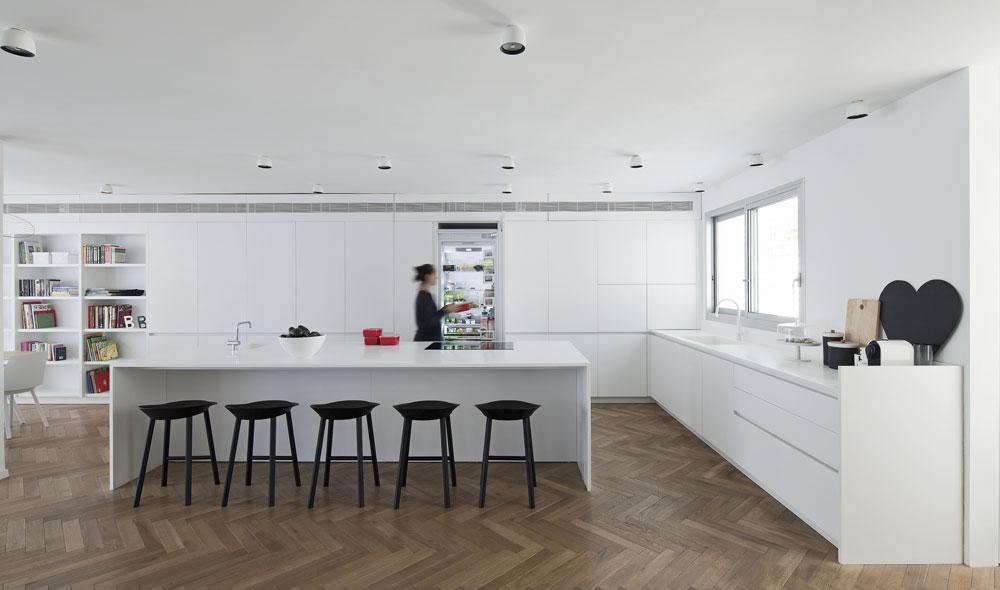 """המטבח הורחב על חשבון הכניסה ותוכנן בצורת האות ר'. בגלל התקרה הנמוכה יחסית נבחרו מנורות ''טכניות'' (ולא תלויות), שפוזרו בקווים מקבילים לארונות ול""""אי"""" (צילום: עמית גרון)"""