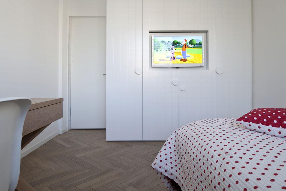 חדרה של הילדה הצעירה. דלתות הארון מחורצות, והידיות פוזרו בצורה אקראית ובגדלים משתנים. במרכזו מסך טלוויזיה  (צילום: עמית גרון)