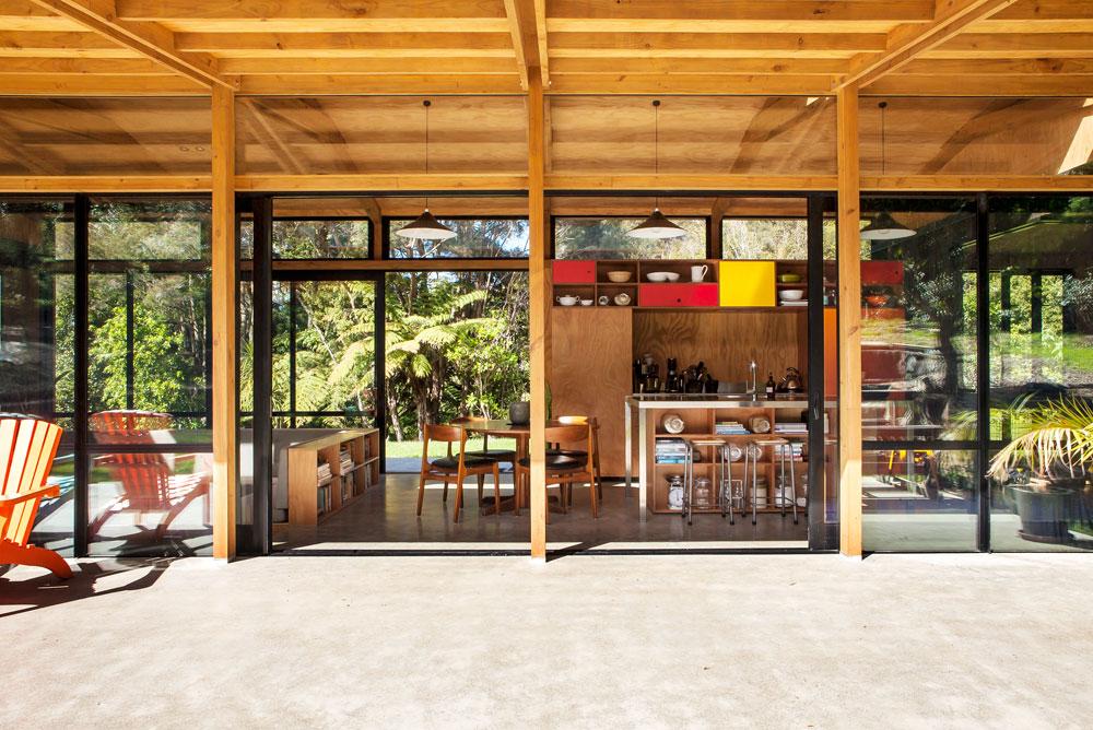 החומרים פשוטים: רצפת בטון שנמשכת מבפנים החוצה ויוצרת אשליה של מרחב גדול יותר, ארונות מטבח שימושיים מדיקט, ופינת ישיבה שקועה, במפלס נמוך יותר, שתחומה בגבה בספרייה (צילום: Emma-Jane Hetherington)