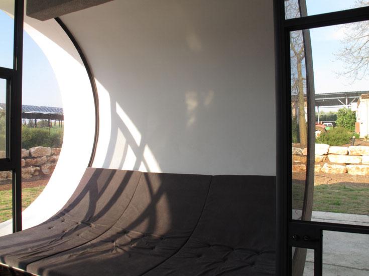 מצידו הפנימי של הקיר העגול בסלון נבנה ספסל יצוק, שעליו הונחו כריות אפורות המתעגלות עם הקיר (צילום: דוד עדיקא)