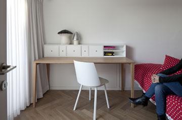חדרה של האחות הגדולה, בעליית הגג. שולחן מפלטת עץ אלון ומגירות לבנות עוצב במיוחד (צילום: עמית גרון)