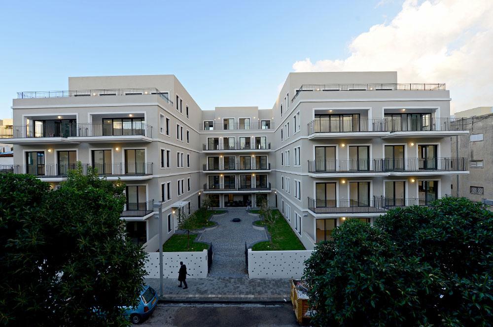 """הבניין מתוכנן בצורת ח', כולל שתי כניסות ומקיף חצר. הדירות בקומת הקרקע נושקות לרצועות דשא. החזיתות שפונות לחצר מזכירות את אלה שמעטרות את הספרים """"והילד הזה הוא אני""""  (צילום: רן בירן)"""