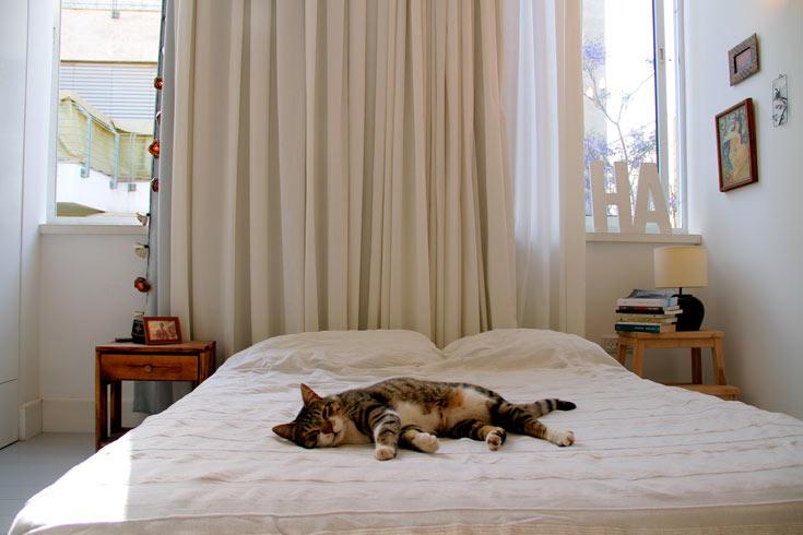 חדר שינה לבן, עם רהיטי צד לא תואמים ומנורה משוק הפשפשים (צילום: ערן ג'גו)