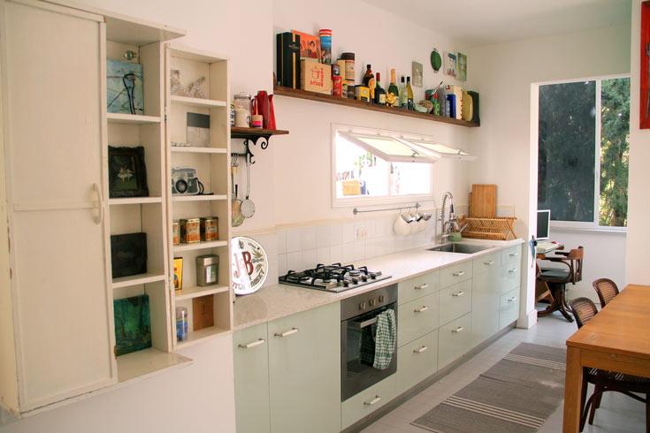 המטבח מורכב מארונות תכלכלים-ירקרקים, מדף עץ עליון ועבודות אמנות של פקט (צילום: ערן ג'גו)