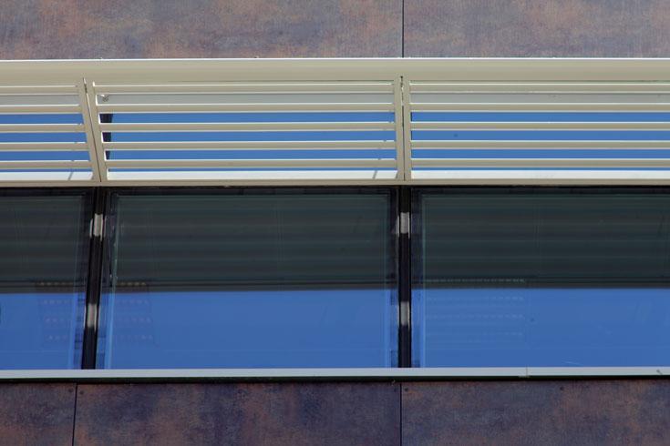 החזיתות מחופות פלדה, זכוכית ופורמייקה עבה בגוון חום. רפפות מצלות על חלונות הכיתות (צילום: אמית הרמן)
