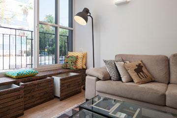 ספה מהדירה הקודמת, כריות אקלקטיות וספסל שמשמש גם לאחסון (צילום: אביעד בר נס)