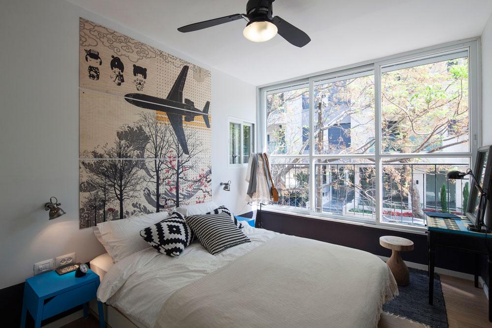 בחלקם התחתון של הקירות נצבע פס עבה בשחור עם פיגמנט סגול. משני צדי המיטה מנורות ושידות צד מ''איקאה'', שרגליהן קוצצו בהתאם לגובה המיטה. על הקיר הדפס בסגנון יפני על שלושה לוחות עץ, שיצרו המעצבים. ליד החלון הגדול שולחן שנקנה בשוק הפשפשים, שעליו ריססו, באמצעות שבלונות, דוגמה בשחור ובטורקיז (צילום: אביעד בר נס)