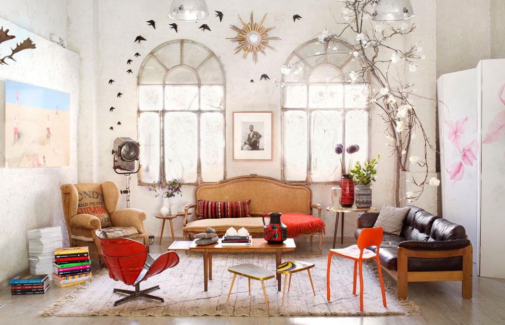 חלונות צרפתיים שפורקו ממבנה ישן עוטפים את הפתחים המרובעים, התעשייתיים, במסגרת רומנטית. מימין עץ עם פרחים לבנים מלאכותיים, הספה עתיקה, הכורסאות וינטג' ועל הקיר ממריאות ציפורים מצוירות (צילום: Manolo Yllera)