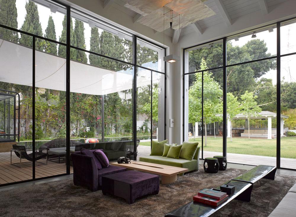 גם בסלון קירות זכוכית עצומים, תקרת עץ גבוהה שממנה תלויה מנורה של המעצב הגרמני המפורסם והוותיק אינגו מאורר ורהיטים אלגנטיים ויקרים (צילום: עמית גרון )