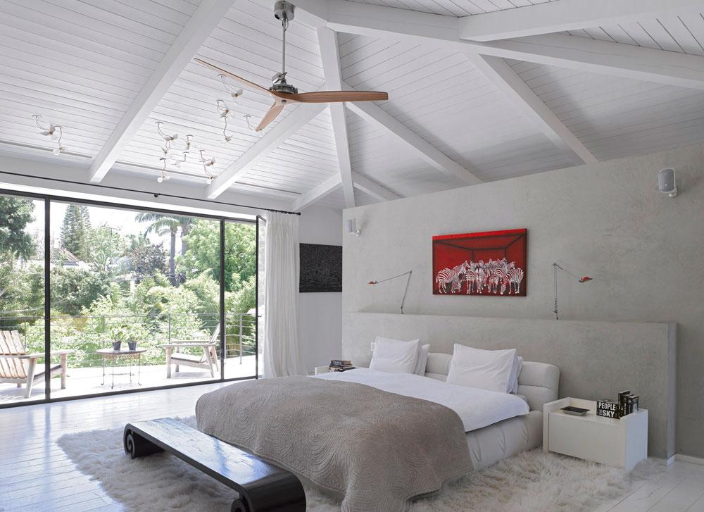 וזו סוויטת השינה שבקומת העליונה. כולה לבנה - מתקרת העץ ועד רצפת הפרקט - ובמרכזה קיר שטויח בגוון חאקי בהיר. מצדו האחד המיטה, ומצדו השני חדרי הארונות והרחצה (צילום: עמית גרון )