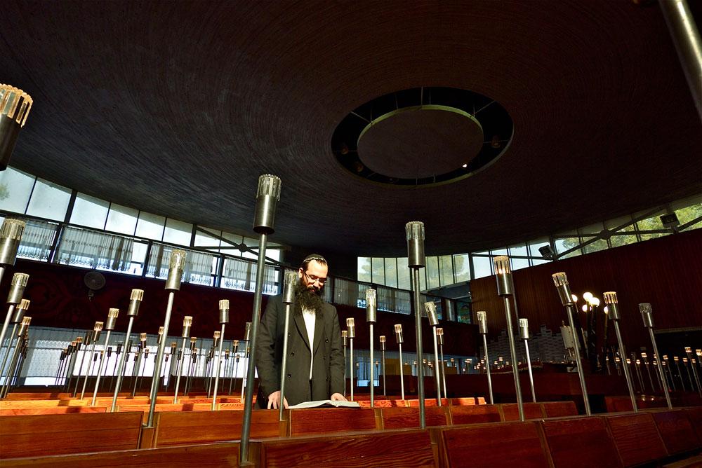 האדריכל יוסף מושלי עיצב את הריהוט והתאורה, על רקע קיר האבנים ורצפת הגרנוליט. לכל שולחן תפילה יש ''נר תאורה'' בגובה אדם, וכך נוצרת רשת נקודות אור (צילום: איתי סיקולסקי)