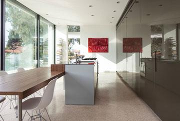 המטבח. ארונות גבוהים מסתירים את כל כלי המטבח ומכשירי החשמל. לדלתותיהם גוון ירוק-אפור, שמגיב לעוצמת האור (צילום: עמית גרון)