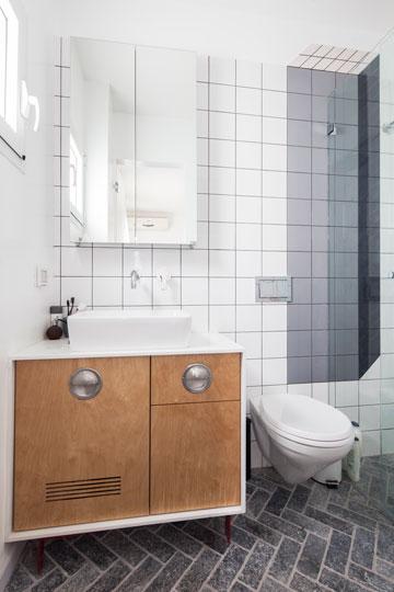 ארון הכיור עשוי עץ בירץ' ממוסגר בשיש קיסר לבן, עם ידיות מטבח תעשייתיות ורגלי פח אדומות (צילום: אביעד בר נס)