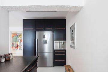 קיר ארונות הגובה מפריד בין המטבח למבואה (צילום: אביעד בר נס)