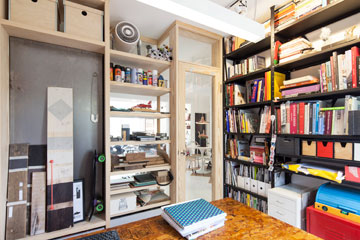 כך זה נראה מתוך המשרד: דלת זכוכית וספריית חומרים שקופה, שלא חוסמות את המבט אל הסלון (צילום: אביעד בר נס)