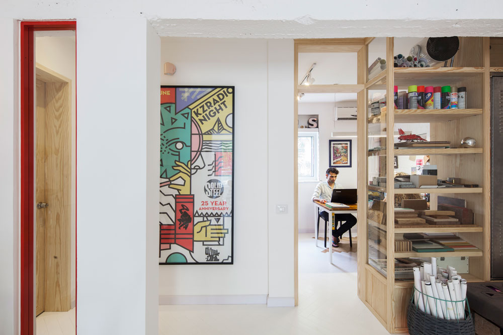 בכניסה למשרד ספריית חומרים ודלת שלא חוסמות את המבט. משמאל דלת הכניסה לחדר ההורים, מצופה באותו פורניר עץ (צילום: אביעד בר נס)