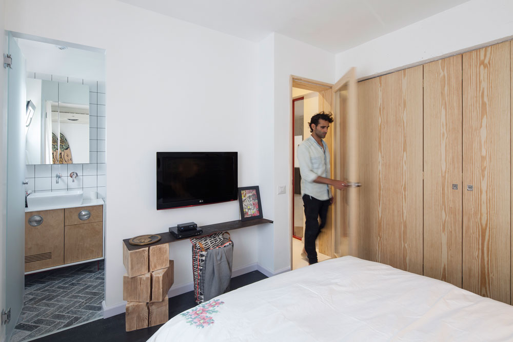חדר הארונות הקטן מוסתר בדלת עץ מתקפלת. הרהיט מתחת למסך הטלוויזיה מורכב ממדף פח שנשען על קוביות של עץ גושני (צילום: אביעד בר נס)