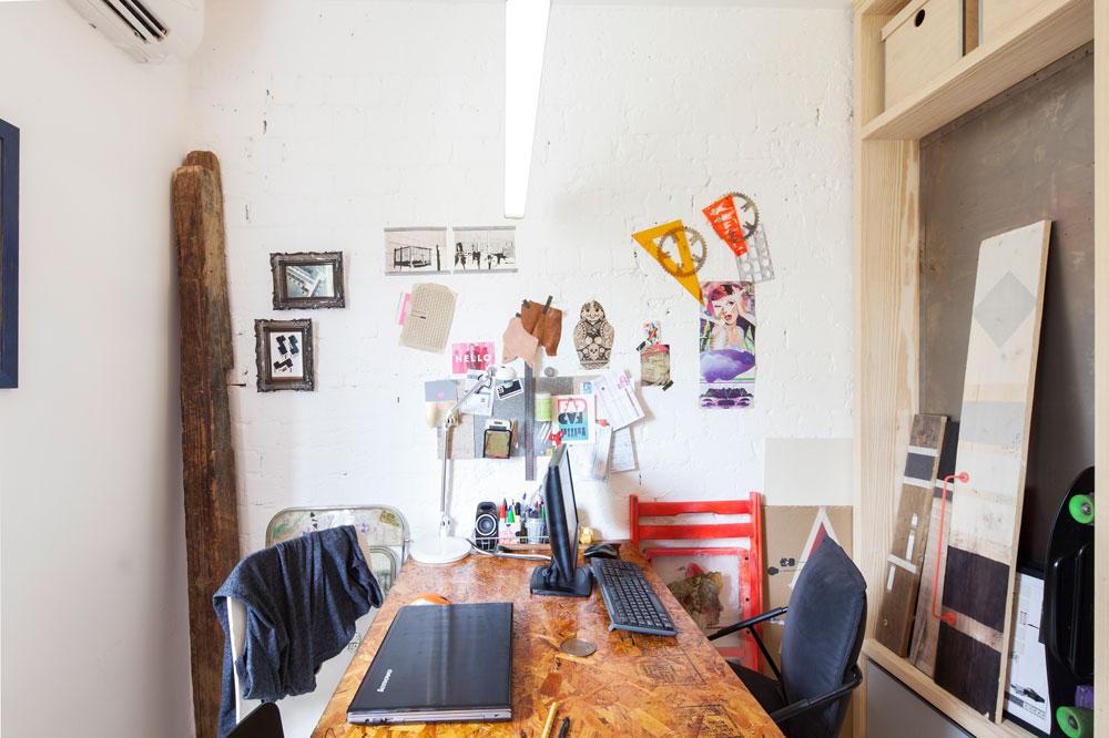 המשרד של בני הזוג: שולחן אחד, שתי עמדות מחשב, קיר לבנים שנחשף בשיפוץ ונצבע לבן, וקורת עץ שנלקחה מנגרייה בפלורנטין, להשלמת המראה התעשייתי (צילום: אביעד בר נס)