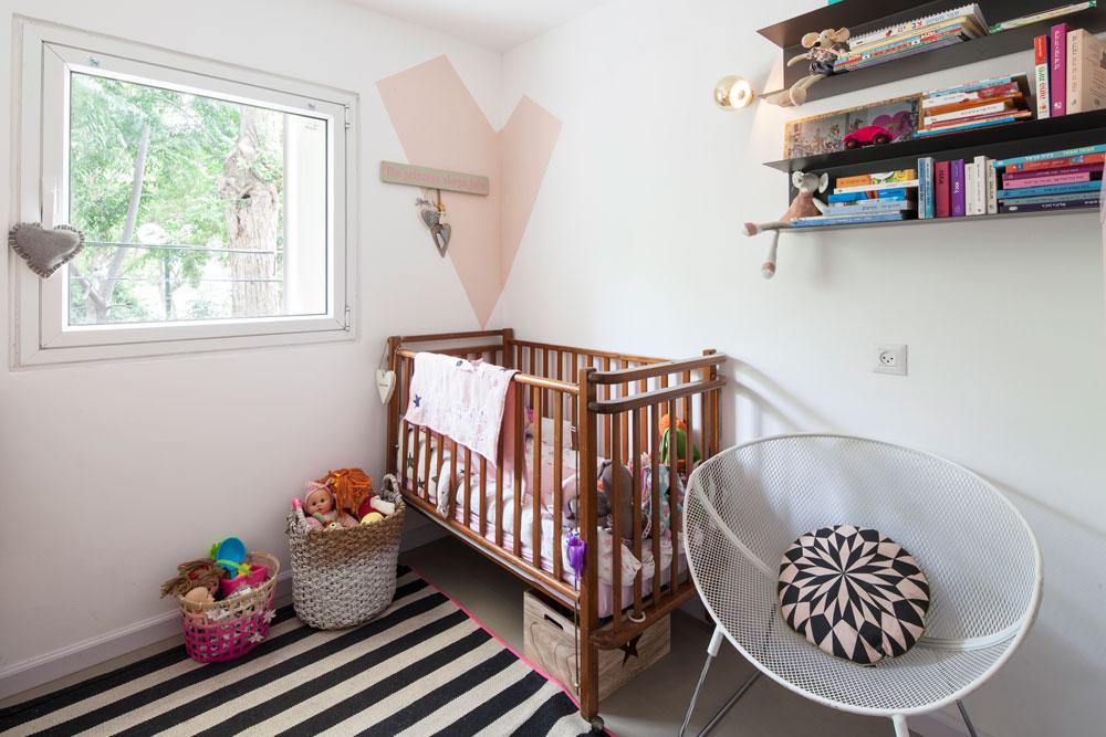 בחדר הילדה שימוש יצירתי בפריטים מאיקאה (מדפי פח שמשמשים כספרייה, למשל), ותוספות של ההורים, כמו הלב הוורוד בפינה מעל המיטה (צילום: אביעד בר נס)