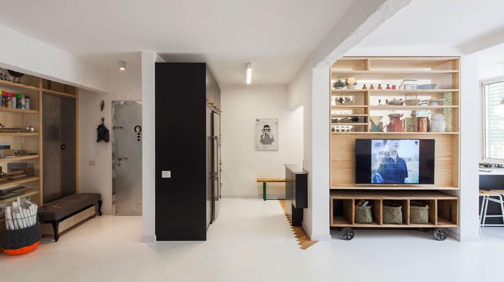 מבט ממרכז הדירה. משמאל המבואה והמשרד המשמש את זוג המעצבים, מימין המטבח והסלון. הארונות הגבוהים הוצמדו לקיר שמפריד בין המבואה למטבח (צילום: אביעד בר נס)