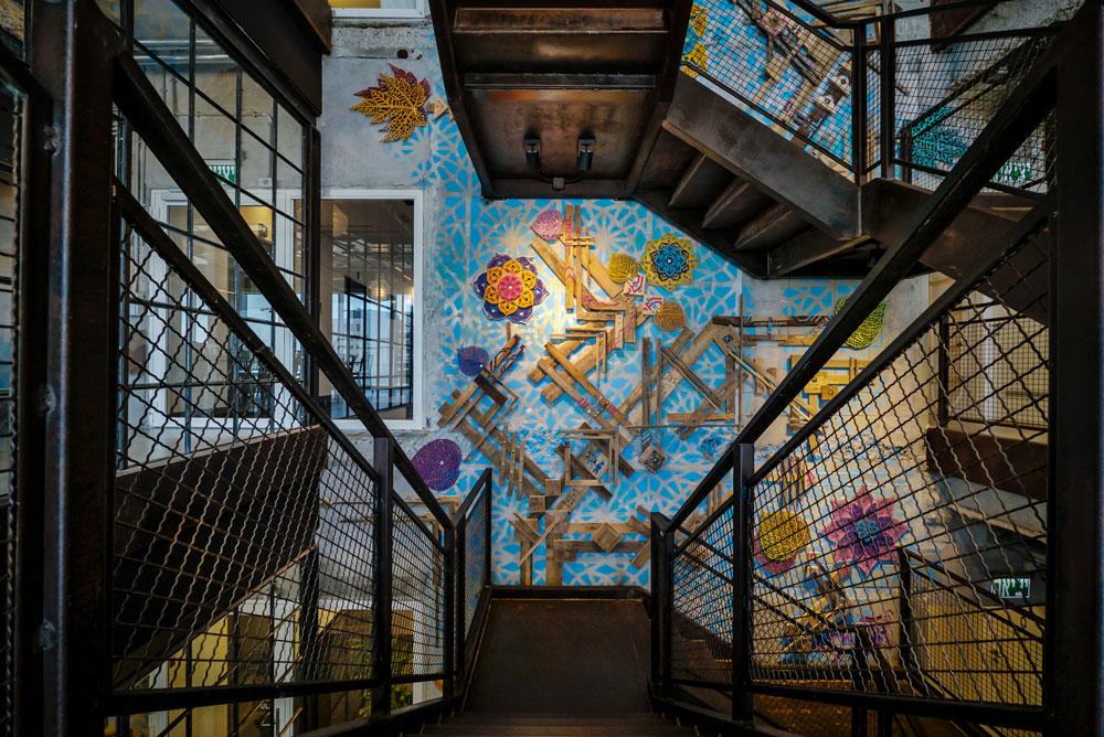 גרם המדרגות הכמו-תעשייתי, כמקובל בחללי המשרדים האופנתיים בשנים האחרונות, מתהדר בעבודה של איתמר פלוג'ה: איורי גרפיטי צבעוניים משולבים באלמנטים מעץ. קיר הערבסקות עשוי בטון (צילום: איתי סיקולסקי)