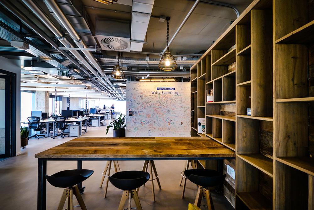 הכתובת על הקיר: ה''וול'' הפייסבוקי המתבקש נמצא כאן בפורמט גדול במיוחד, וברקע נראות עמדות העבודה (צילום: איתי סיקולסקי)