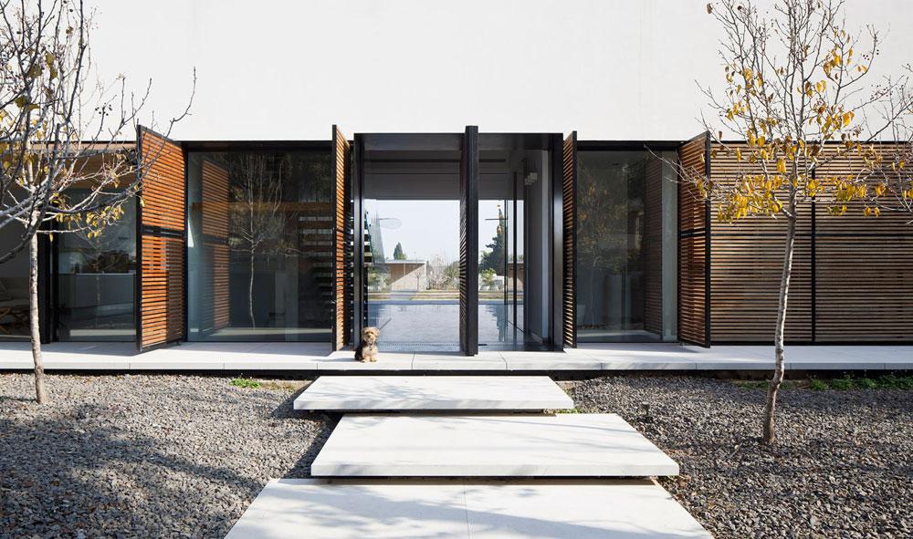 מדלת הכניסה אפשר לראות הישר דרך הבית והרחק עד לקצה המגרש. סרגלי העץ הם למעשה מערכת תריסים חכמה ודינמית, שמאפשרת לפתוח כל תריס בנפרד לפי הצורך בפרטיות, האור והעונה (צילום: עמית גרון)
