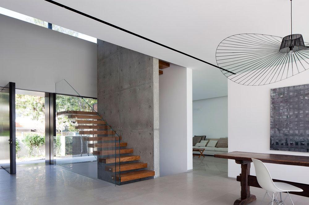 קיר מבטון חשוף מתנשא לכל גובה הבית. על הקיר נתלו מדרגות מרחפות מעץ טיק, שנתחמו במעקה זכוכית שקוף (צילום: עמית גרון)