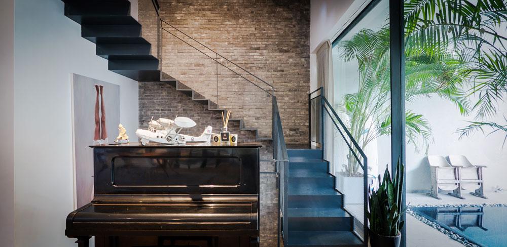 """קיר זכוכית בצורת האות ר' מפריד בין הבריכה לסלון ולגרם המדרגות, שעשויות פלדה מכופפת בעובי 12 מ""""מ ושנתלו על קיר לבנים (צילום: איתי סיקולסקי)"""