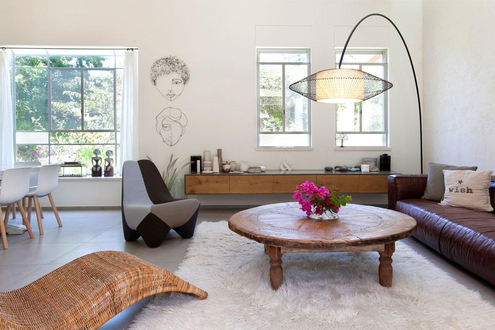 בסלון נטול הטלוויזיה רהיטים שאספה וייסמן במשך השנים: ספת עור חומה (''סיאם''), שולחן עגול (''Uma''), כיסא שמזכיר לוייסמן את מתווה הגוף הנשי (''מורוסו'') וכורסת קש שמהווה חלק מקו ריהוט החוץ של ''איקאה''. מעל השולחן מרחפת מנורה עומדת מקש וברזל (''סיאם''). מתחת לשני חלונות נתלתה שידה, שעליה אוסף כלי קרמיקה (צילום: שירן כרמל )