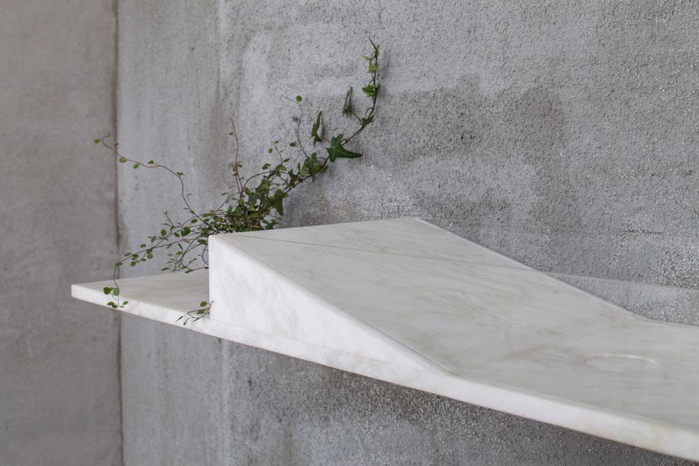 חתיכה אחת של אבן לבנה משמשת ככיור וכמדף, שתלוי על הקיר. דפנות הכיור עשויים זכוכית שקופה (צילום: עמית גרון)