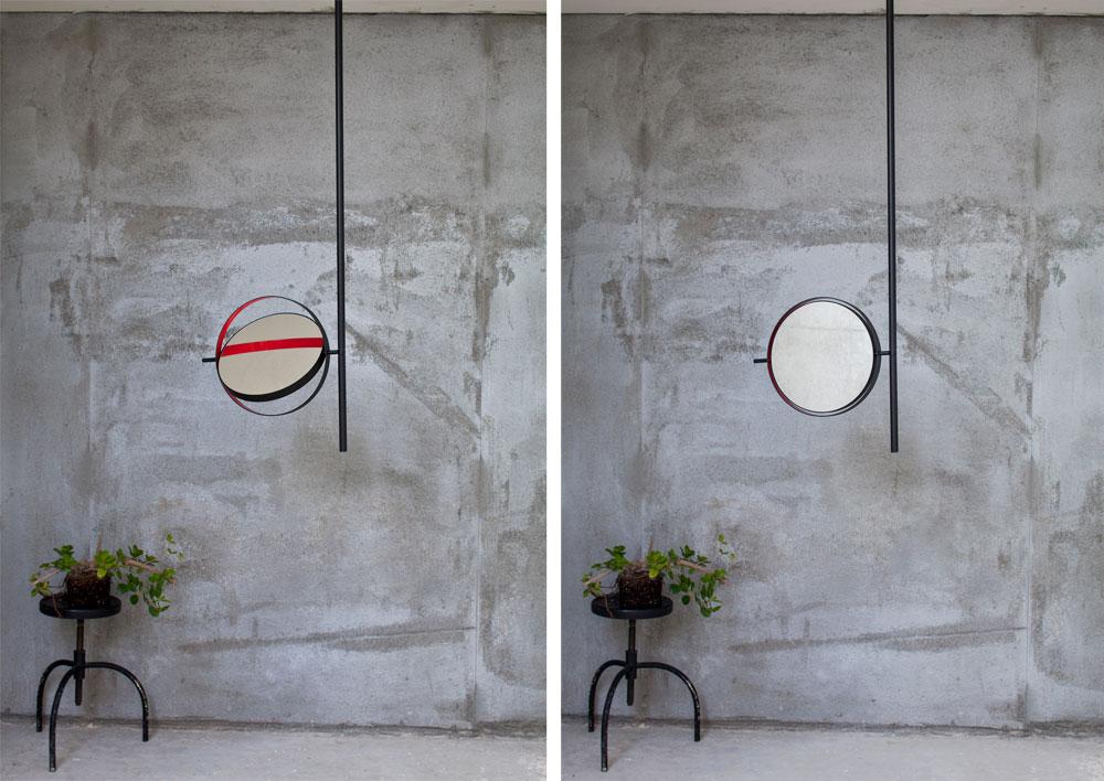 מראה עגולה ודו-צדדית מברזל מושחר מחוברת לתקרה באמצעות צינור ומותקנת על טבעת, שחלקה הפנימי צבוע באדום. הצבע העז נגלה עם תנועת המראה (צילום: עמית גרון)