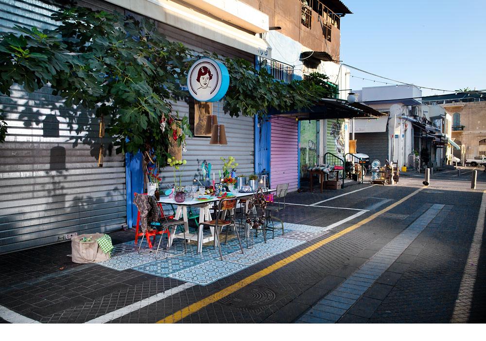 הצבעוניות של שולחן החג שואבת השראה מהסביבה: תריסי פח סגורים, צמחייה, גרפיטי ופריטים שניתן למצוא בשוק – ''רדי מייד'', ברזל, חומרים ממוחזרים וכלי פלסטיק זרחניים (צילום: ענבל מרמרי)