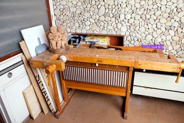השולחן שניצב בכניסה למשרד על רקע קיר חלוקי הנחל (צילום: ענבל מרמרי)